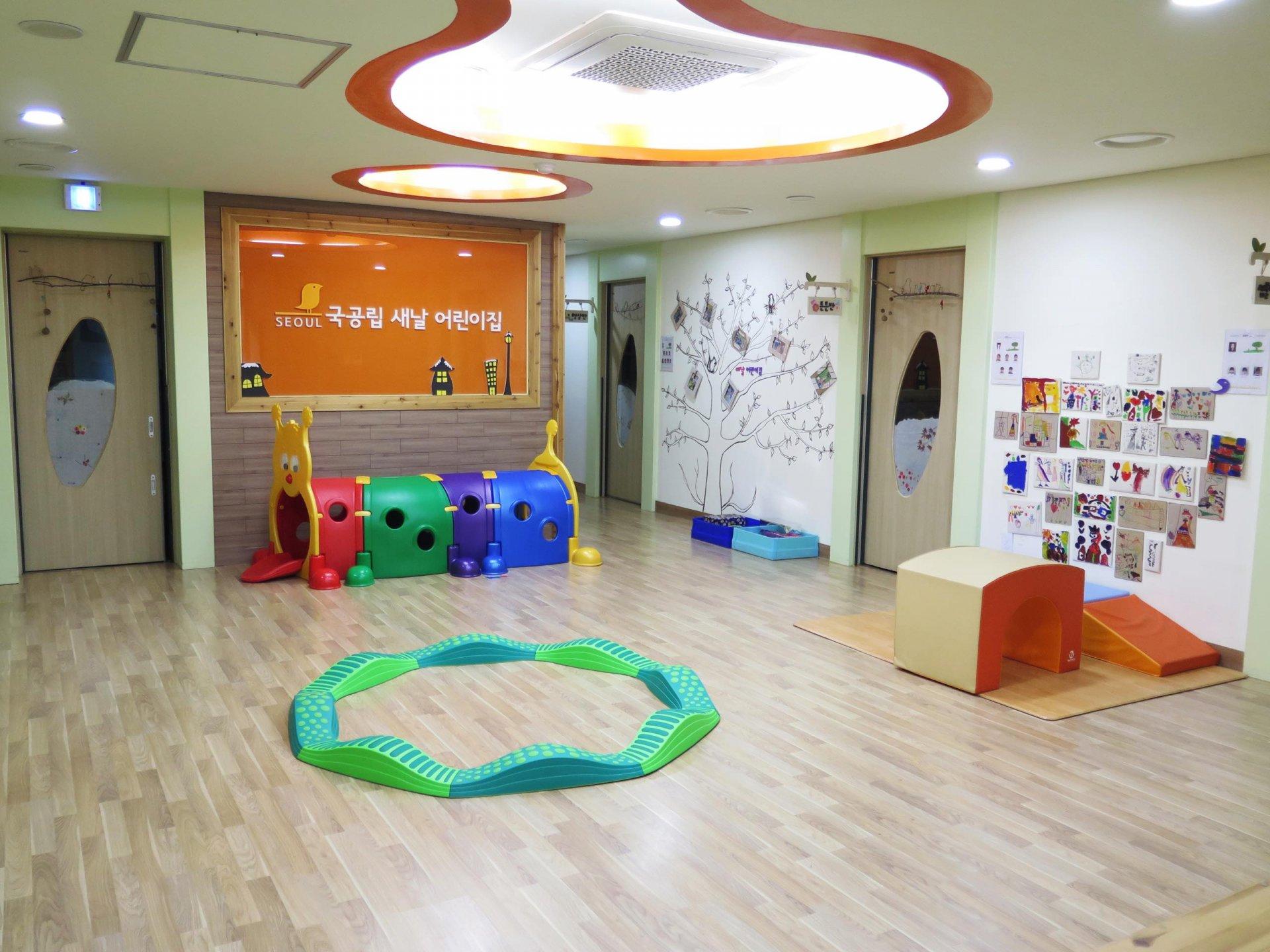 마룻바닥에 어린이 놀이용품이 보이고, 벽에 새날어린이이집이라는 글씨가 쓰여있다.