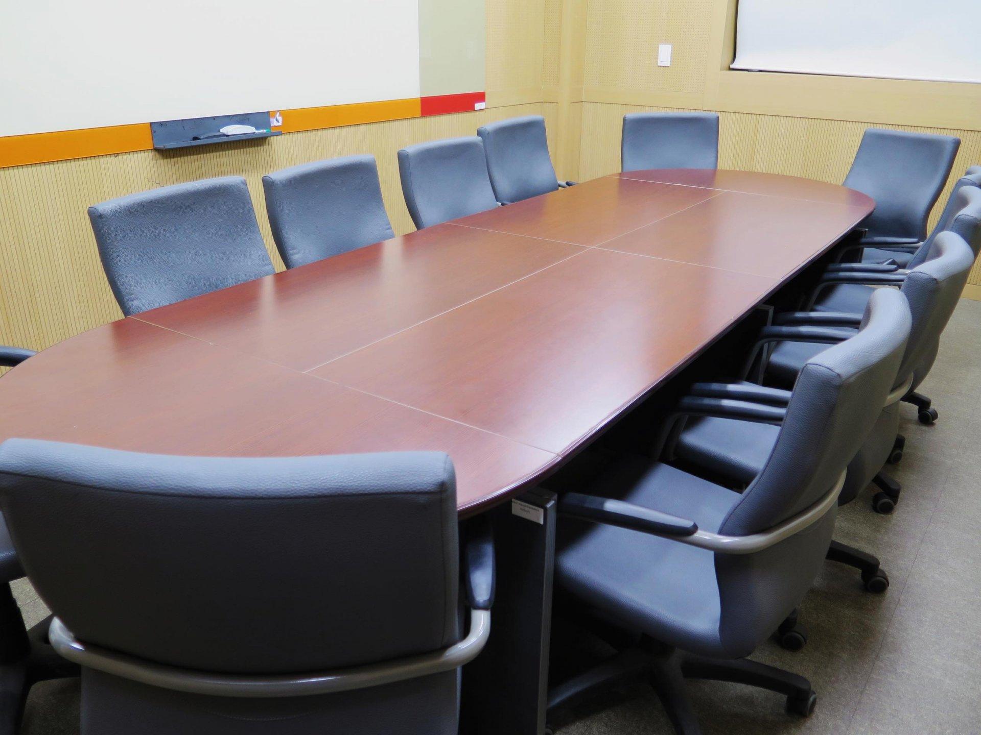 긴 책상을 주변으로 의자가 둘러쌓여진 작은 방의 사진