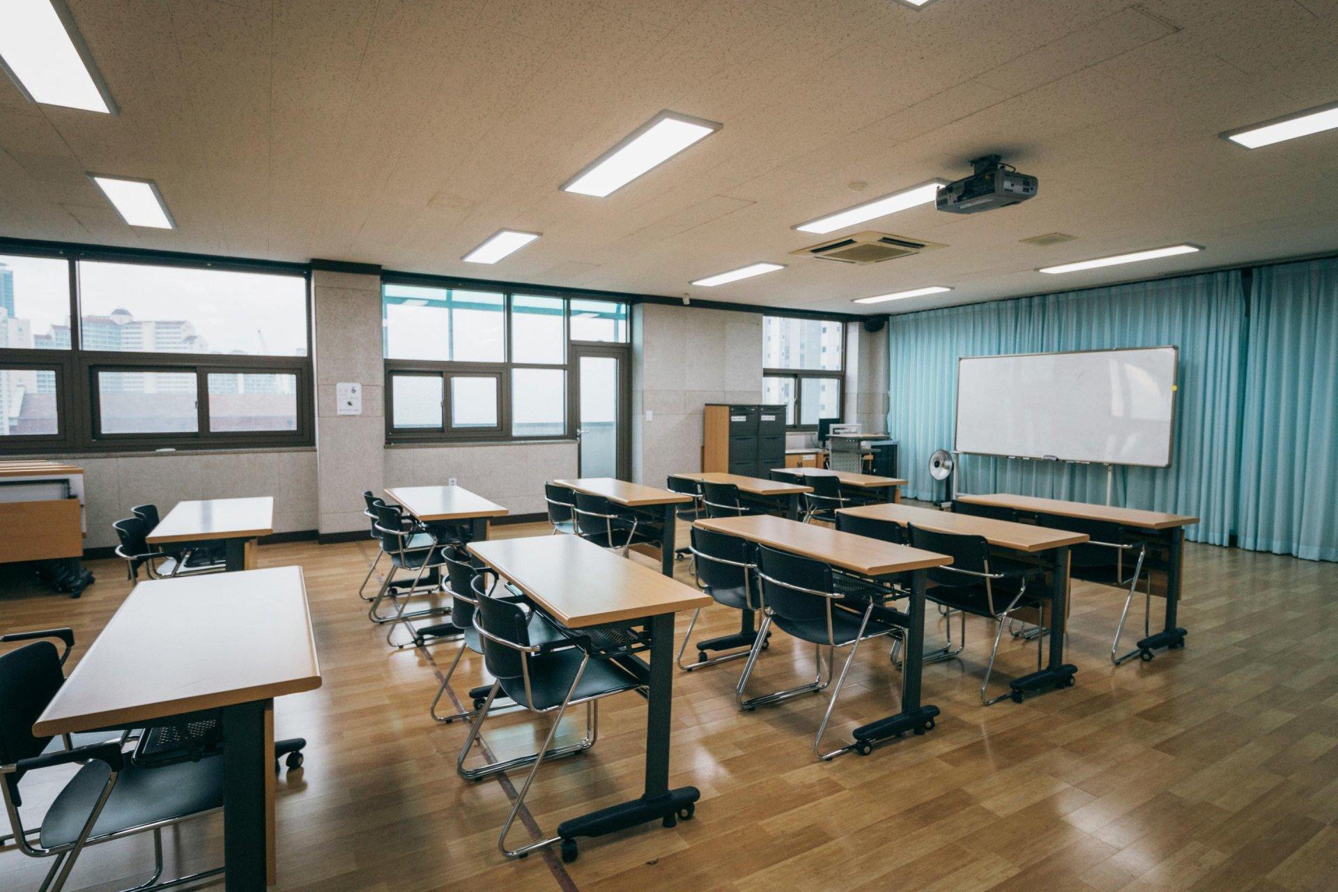 화이트보드가 보이고, 책상이 줄이어 보이는 강의실 .