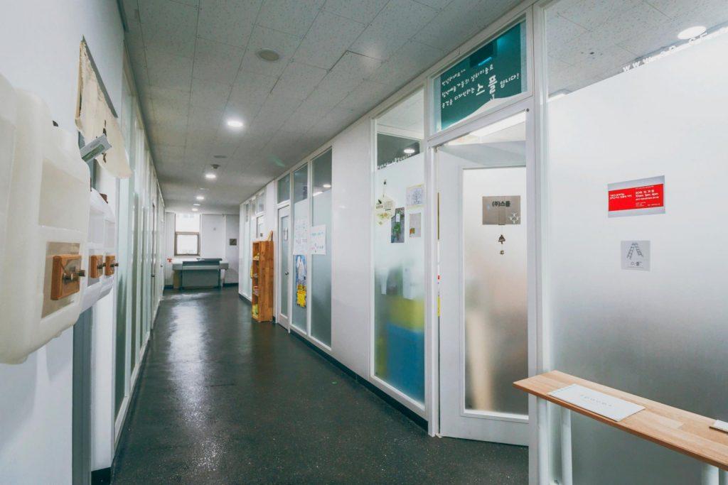 여러 사무실 입구가 보이는 긴 복도.